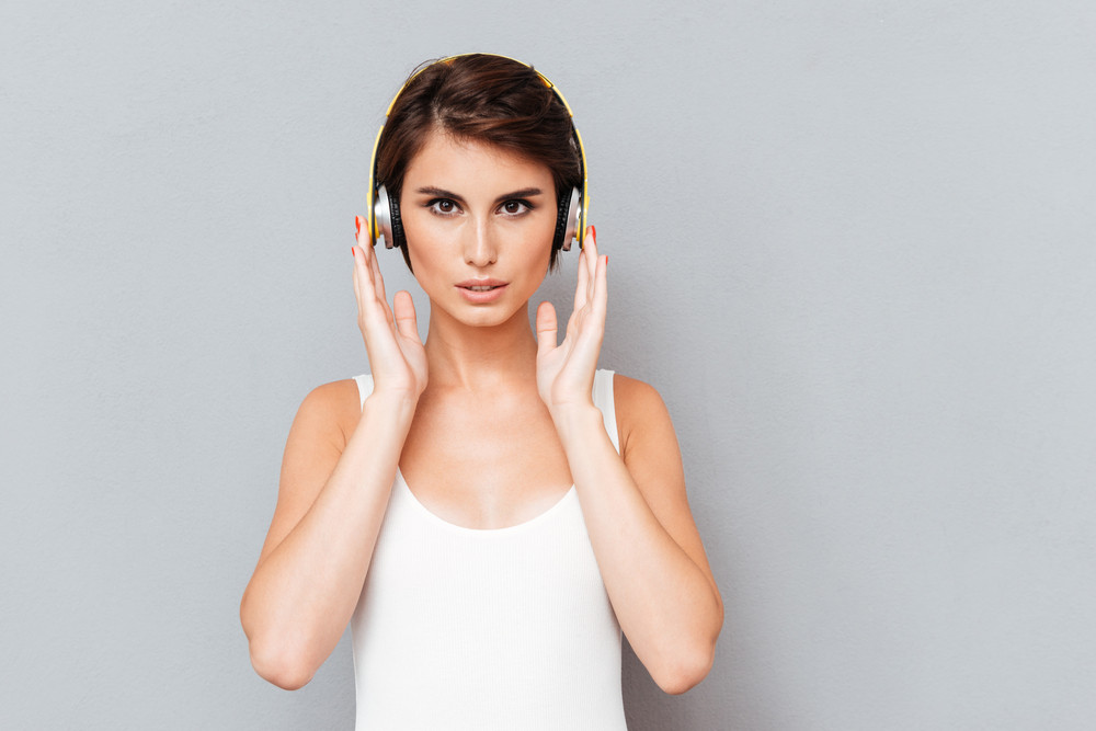 Portrait of a pensive concentrated woman listening music in headphones over gray background