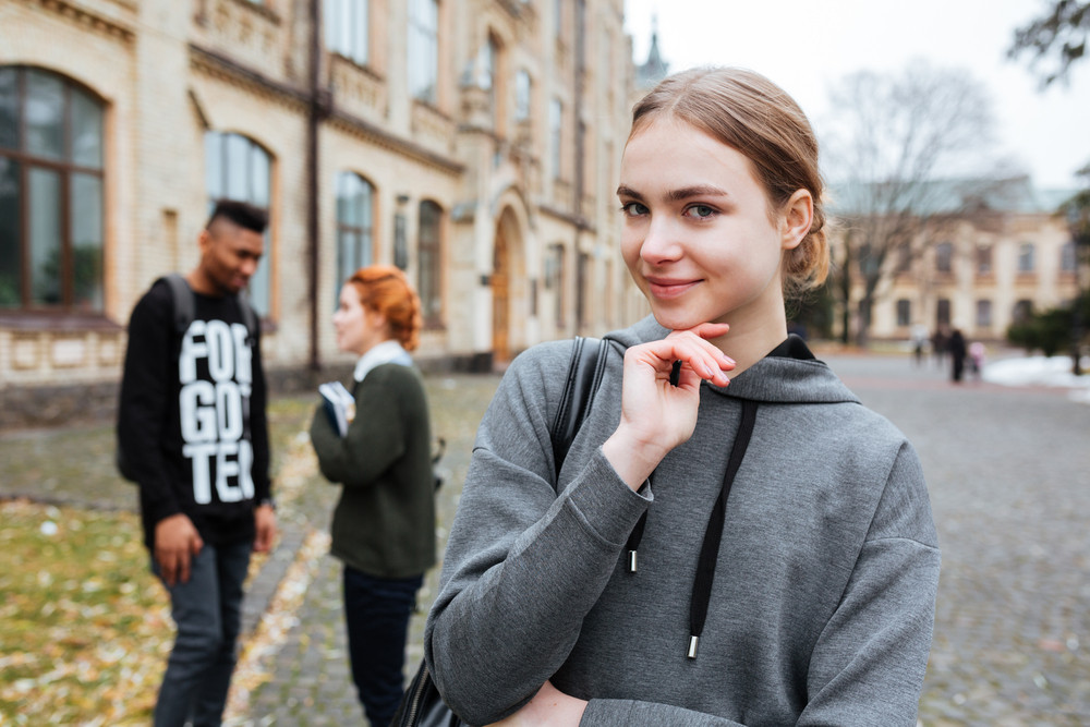 Portrait of a pensive young woman standing outside at the campus and looking at camera