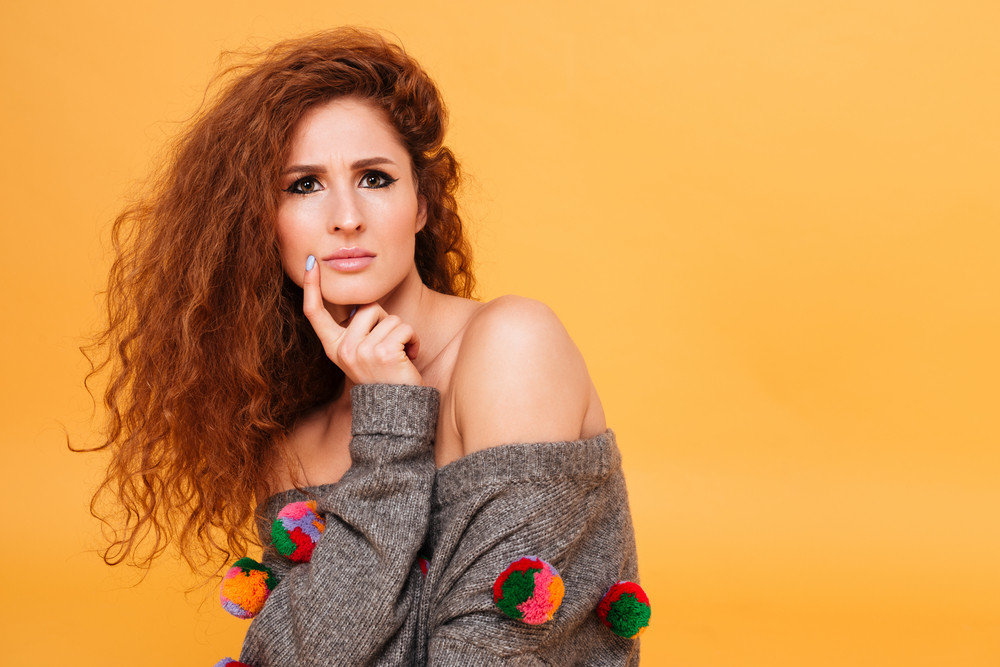 Portrait of a pensive young woman with red hair looking at camera isolated over orange background