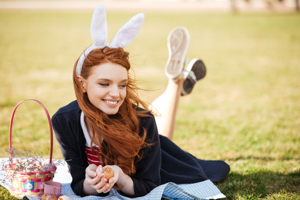 Portrait of a pretty cheerful red head girl wearing easter bunny ears and laying on a grass with basket full of painted eggs