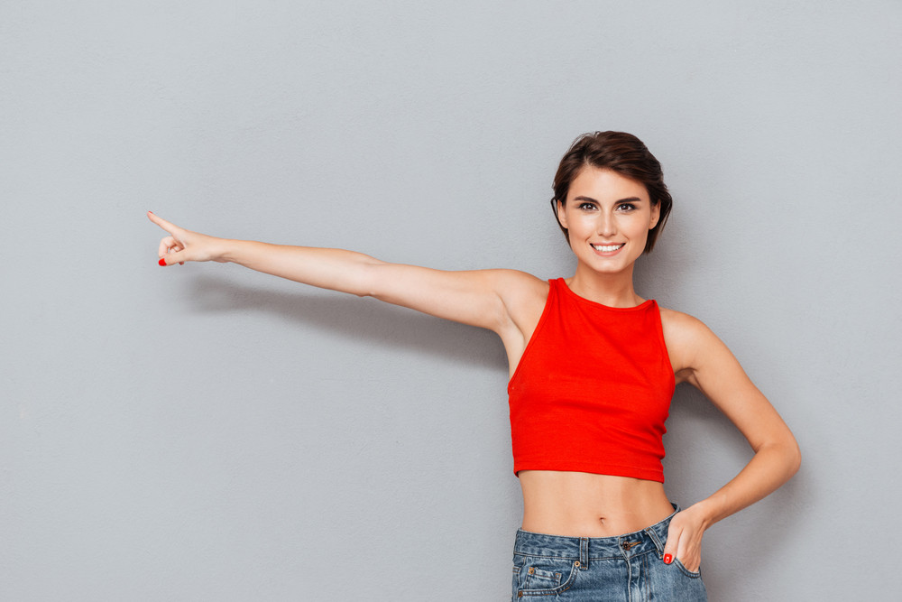 Portrait of a pretty girl in red top pointing finger away isolated on a gray background