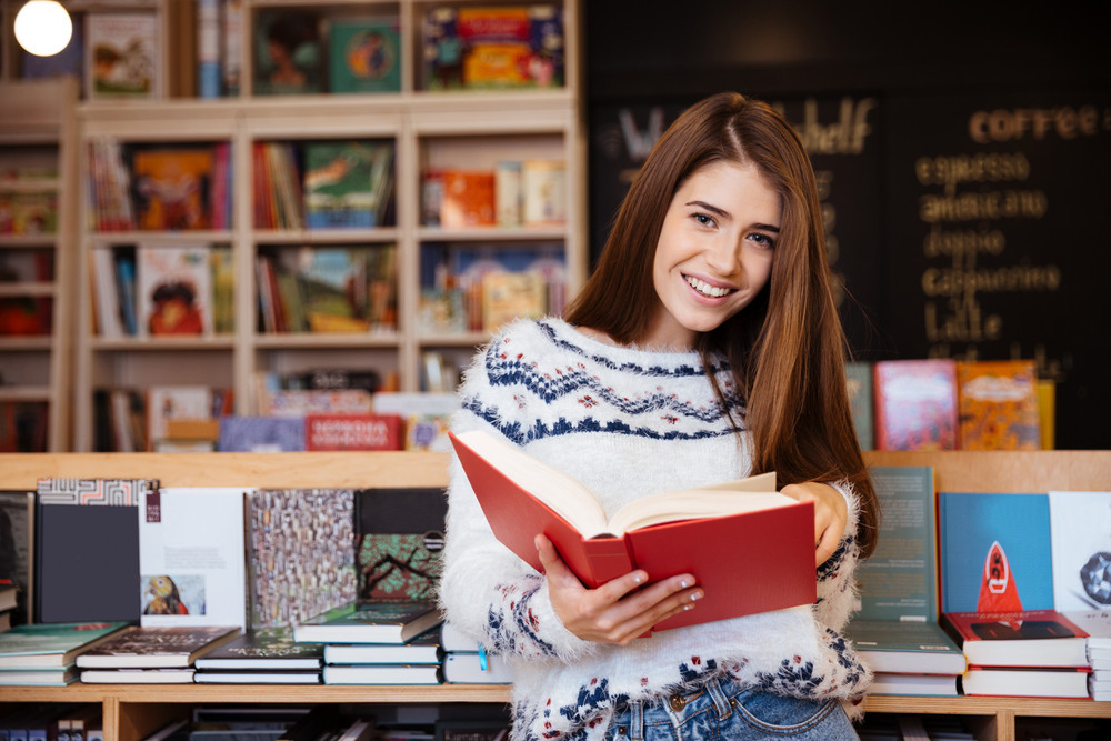 Portrait of a pretty smiling girl reading book indoors in library and looking at camera