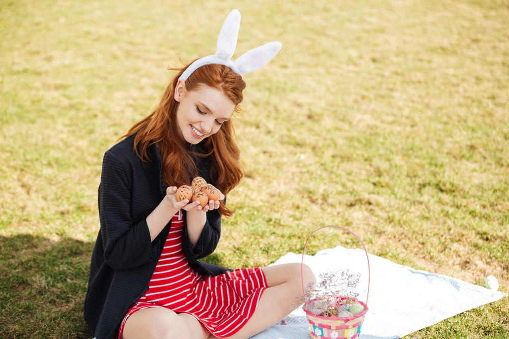 Portrait of a pretty young girl with long ginger hair holding painted easter egg outdoors while having picnic