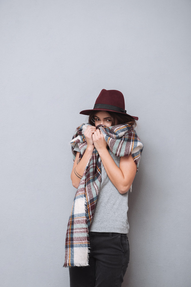 Portrait of a pretty young woman in hat covering her face with scarf isolated on the gray background