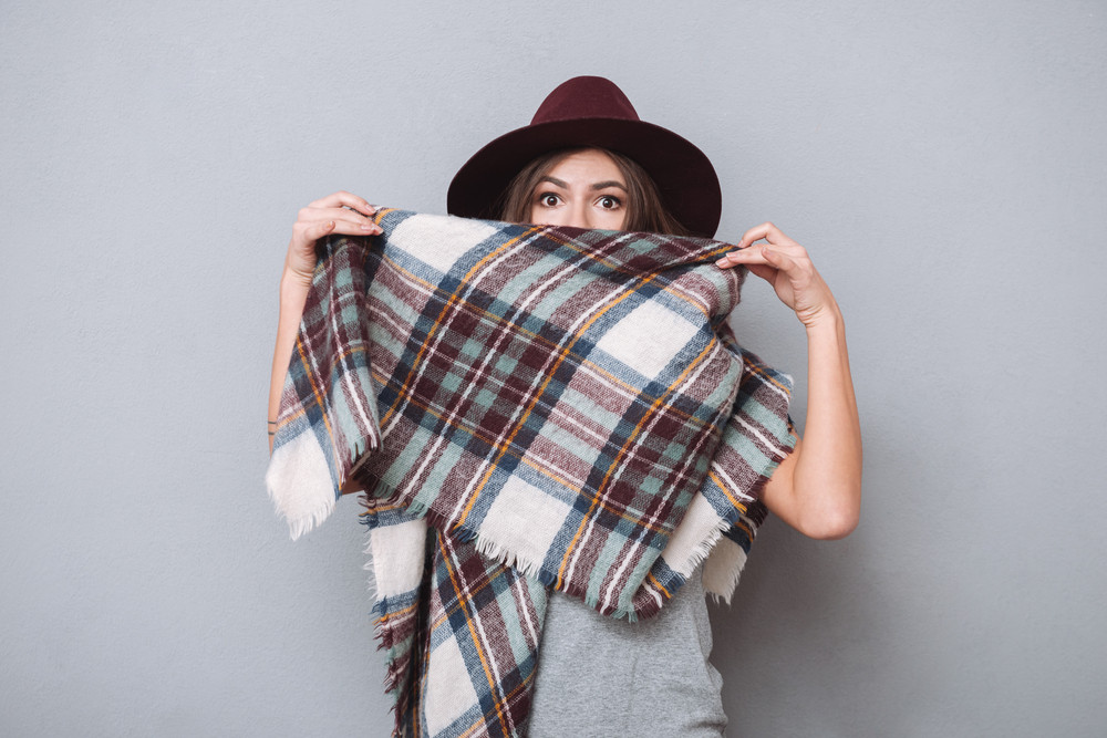 Portrait of a pretty young woman in hat covering her mouth with scarf isolated on the gray background