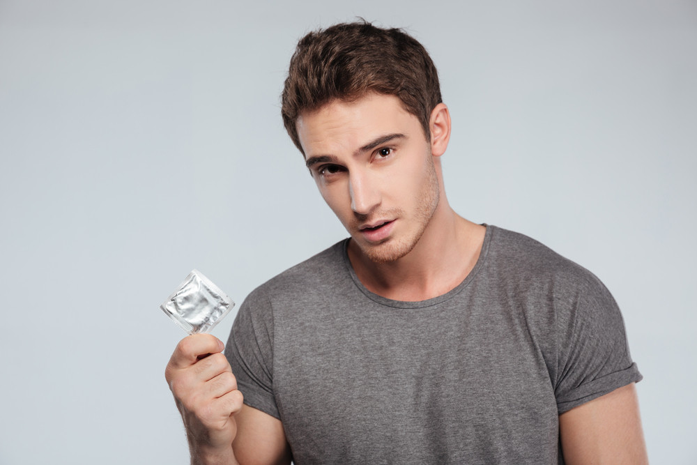 Portrait of a serious man holding condom and looking at camera over white background