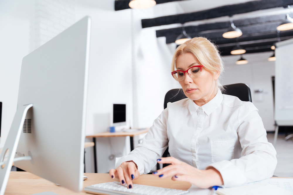 Portrait of a serious mature businesswoman working in office with computer