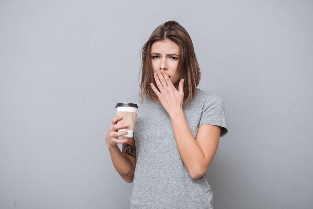 Portrait of a sleepy young girl yawning and holding cup of coffee isolated on a gray background