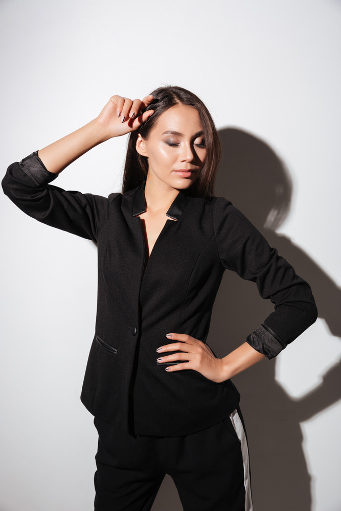 Portrait of a smart attractive woman in black suit standing with eyes closed over white background