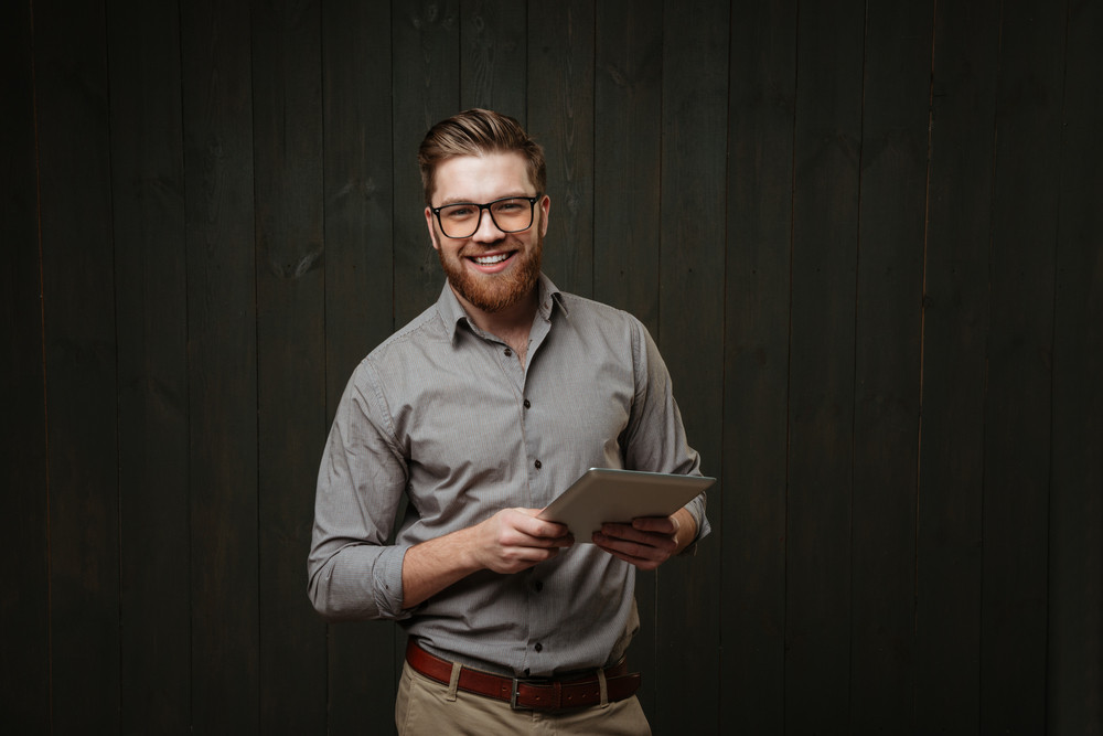 Portrait of a smiling bearded man in eyeglasses holding tablet computer isolated on a black wooden background