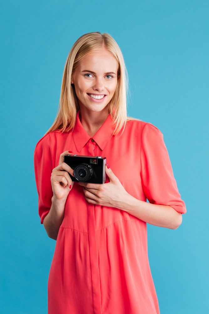Portrait of a smiling blonde woman holding retro camera over blue background