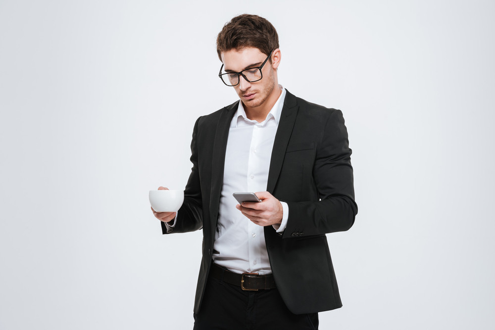 Portrait of a smiling businessman holding cup with coffee and using mobile phone isolated on a white background