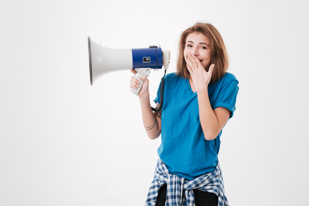 Portrait of a smiling casual girl holding loudspeaker and covering mouth with hand isolated on a white background