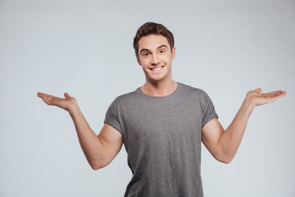 Portrait of a smiling casual man holding copyspace on two palms over white background