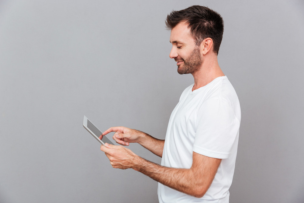 Portrait of a smiling casual man holding tablet computer over gray background
