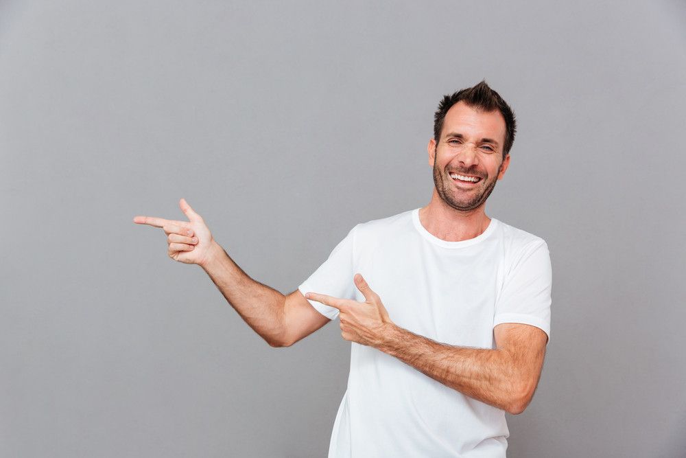 Portrait of a smiling casual man pointing fingers away over grey background