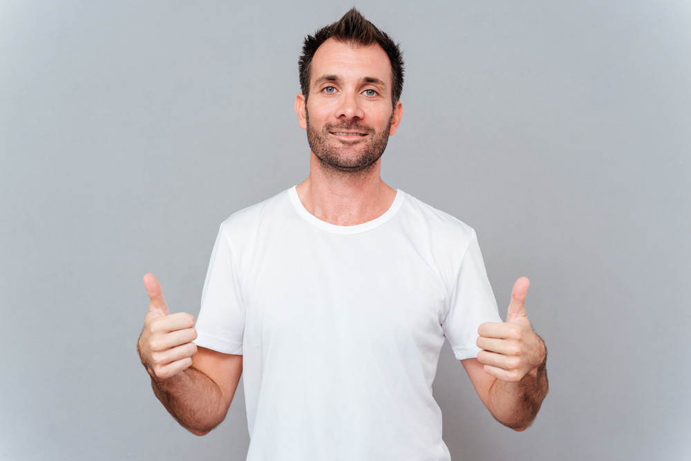 Portrait of a smiling casual man showing two thumbs up and looking at camera over gray background