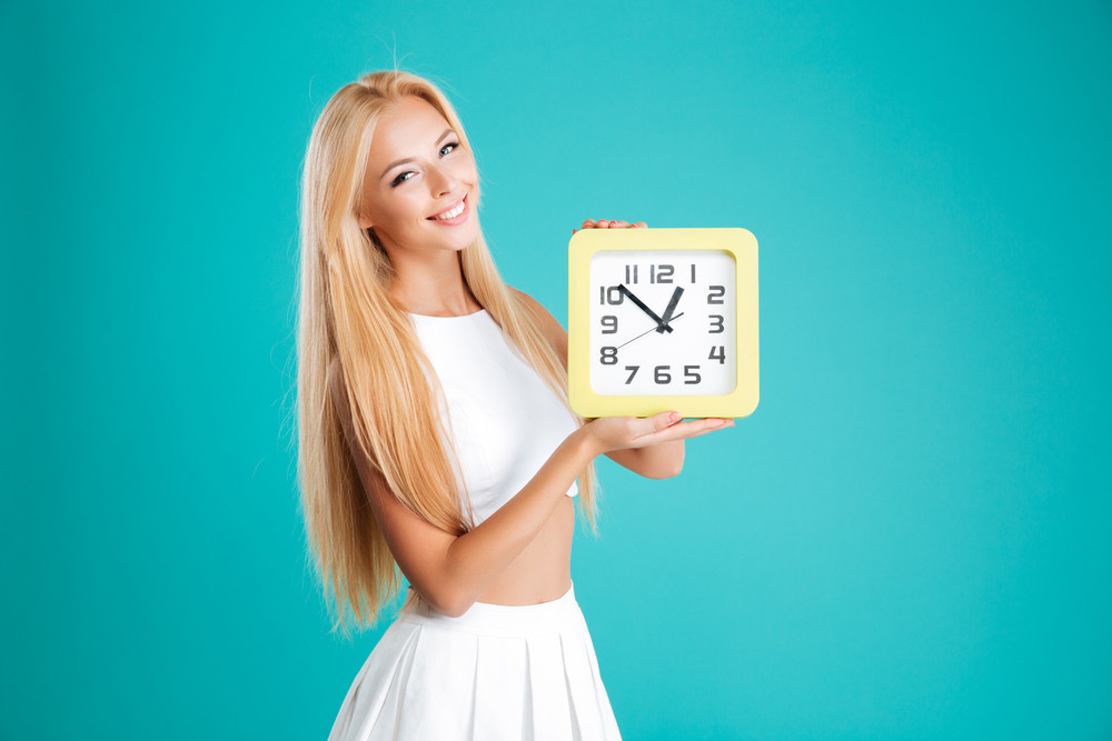 Portrait of a smiling cheerful girl with long hair holding wall clock isolated on the blue background