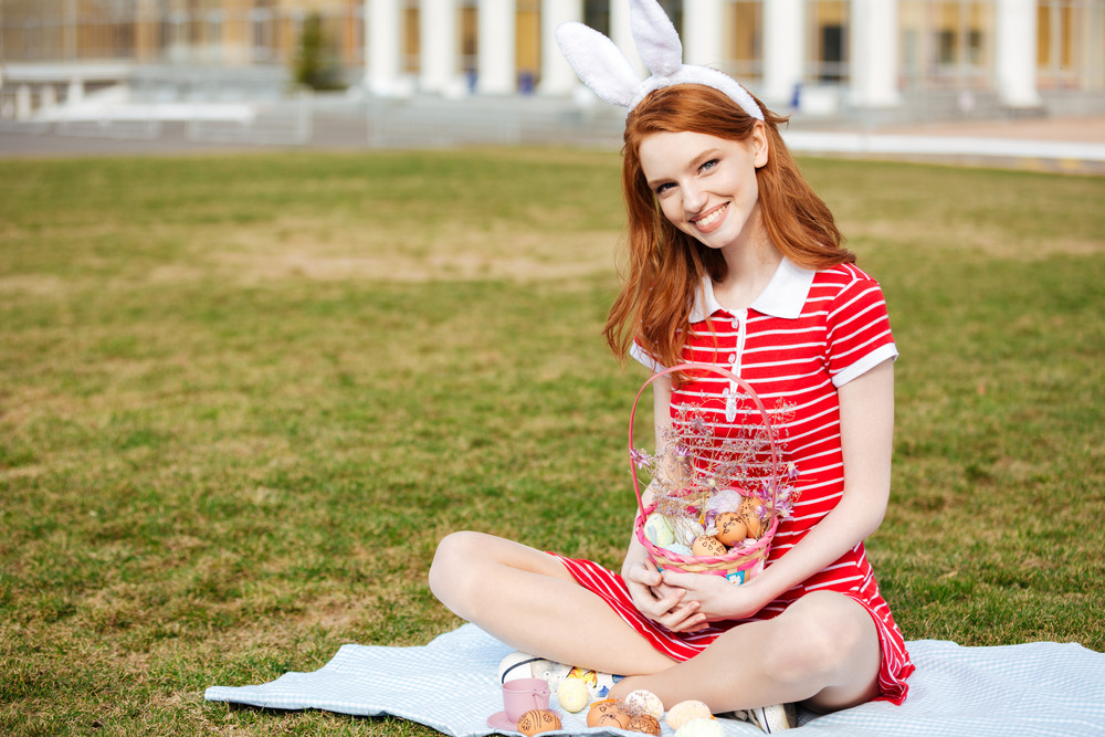 Portrait of a smiling cheerful girl with long red hair wearing bunny ears and holding easter basket with colored eggs outdoors