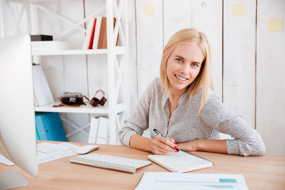 Portrait of a smiling happy business woman sitting at her workplace and making notes