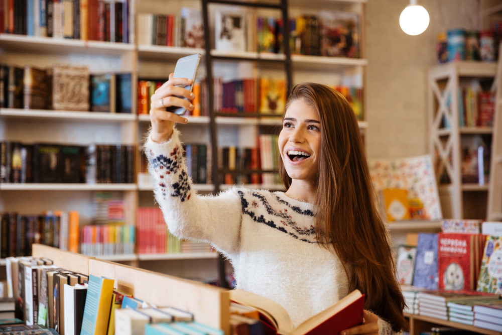 Portrait of a smiling happy girl taking selfie while sitting in library