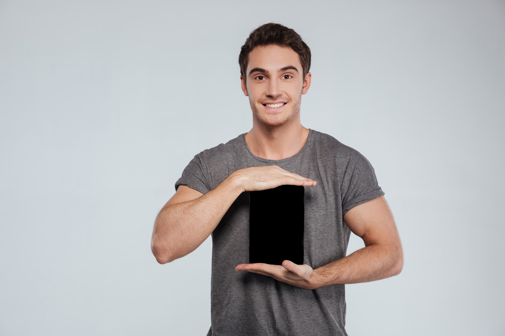 Portrait of a smiling happy man showing blank tablet computer screen over white background