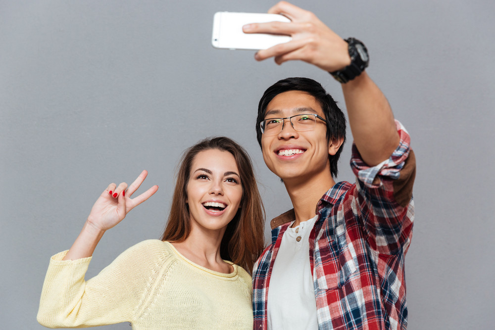 Portrait of a smiling interracial couple making selfie together isolated on the gray background