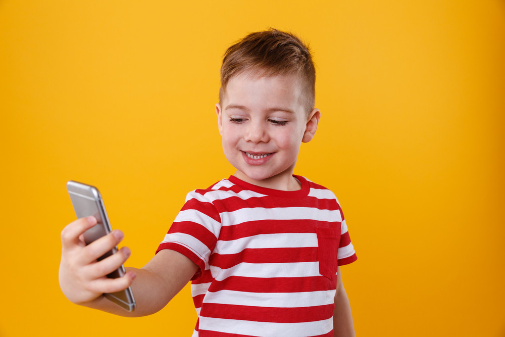 Portrait of a smiling little boy holding mobile phone and making selfie isolated over orange background