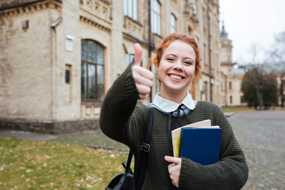 Portrait of a smiling pleased female student holding books and showing thumbs up outside university campus