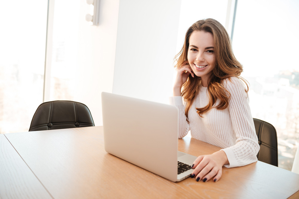 Portrait of a smiling pretty woman working on laptop while sitting at table at home