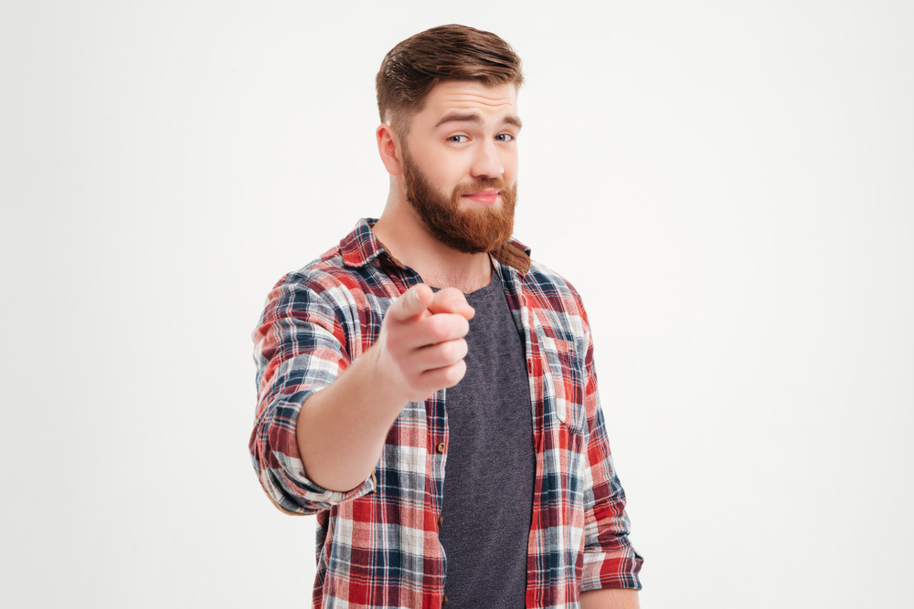 Portrait of a smiling satisfied man in plaid shirt pointing at camera isolated on a white background