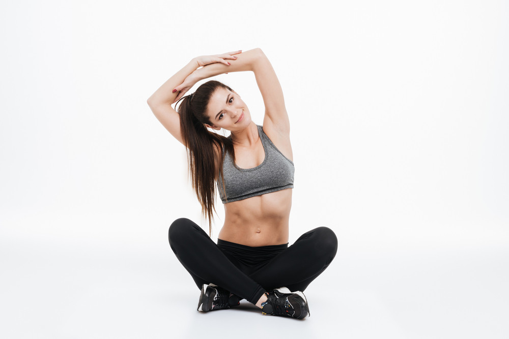 Portrait of a smiling sports woman stretching hands while sitting on the floor isolated on a white background