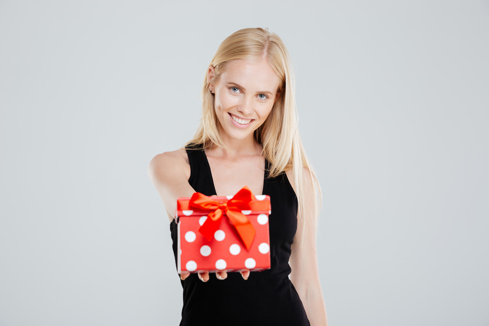 Portrait of a smiling woman in dress holding gift box isolated on a white background