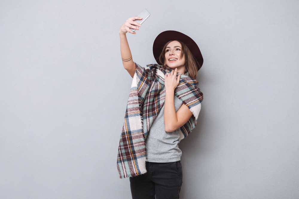 Portrait of a smiling woman making selfie photo on smartphone over gray background