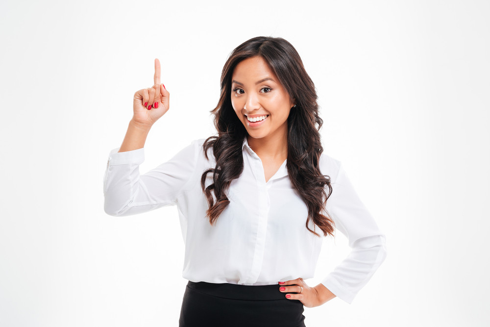 Portrait of a smiling young beautiful asian businesswoman pointing finger up over white background