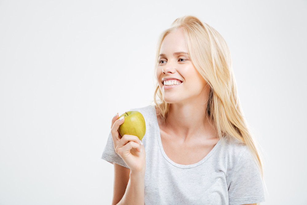 Portrait of a smiling young girl holding green apple isolated on a white background
