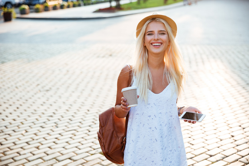 Portrait of a smiling young girl in hat holding take away coffee cup and smartphone walking on the street