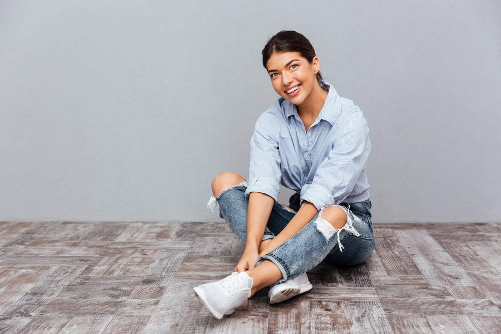 Portrait of a smiling young girl sitting on the floor isolated on a gray background