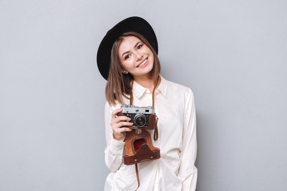 Portrait of a smiling young woman in hat holding retro camera isolated on the gray background