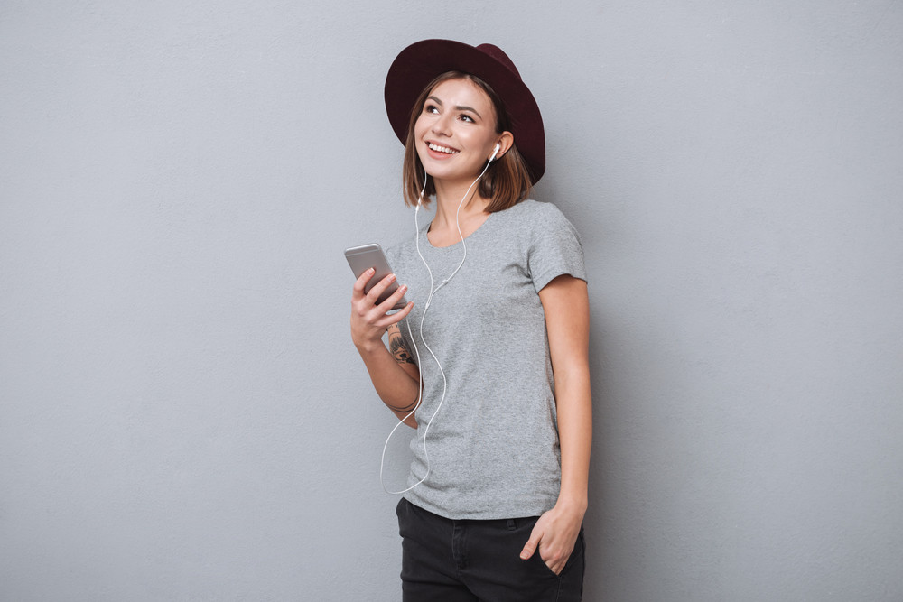 Portrait of a smiling young woman in hat listening music with earphones and mobile phone isolated on a gray background