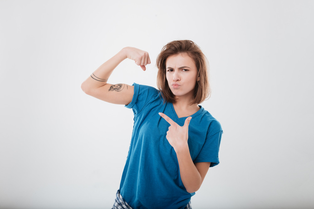 Portrait of a strong young girl showing bicep and pointing finger isolated on a white background