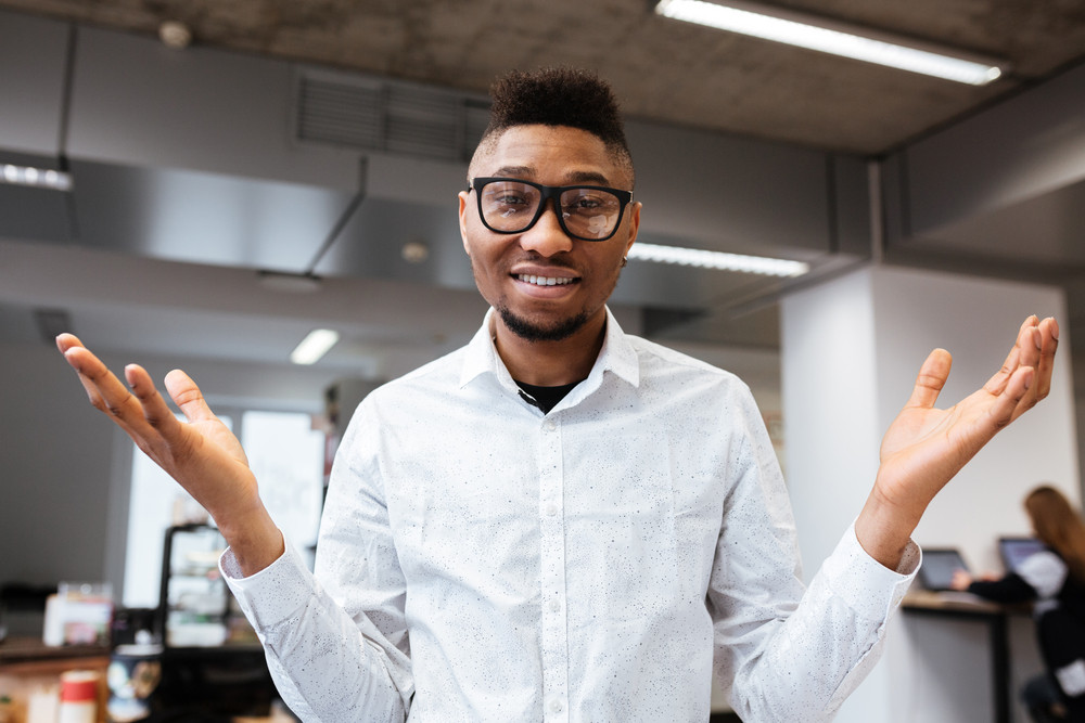 Portrait of a successful african businessman smiling and gesturing with hands. Look at camera.