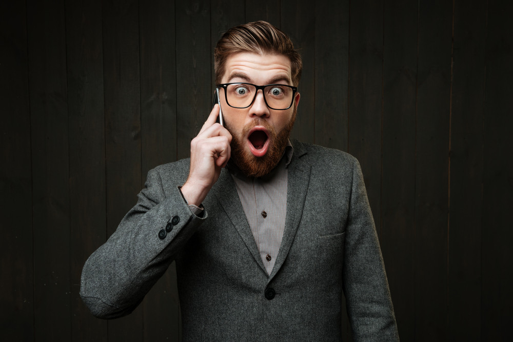 Portrait of a surprised amazed man in eyeglasses talking on mobile phone isolated on the black wooden background