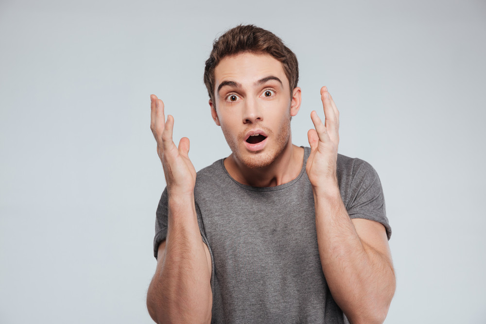 Portrait of a surprised young man holding hands at his face over white background