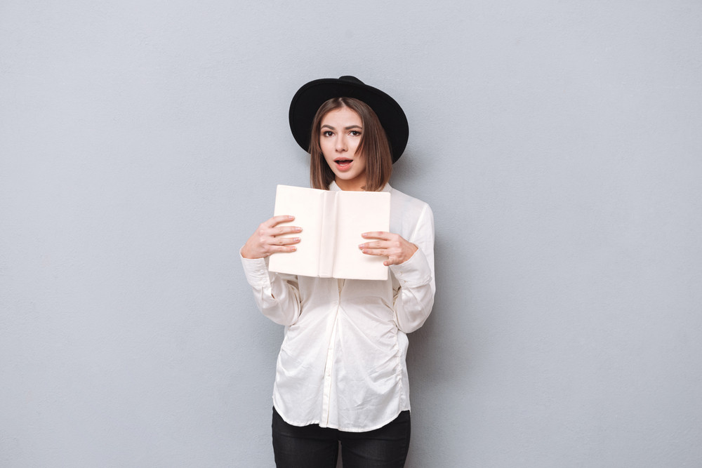 Portrait Of A Surprised Young Woman Holding Book And Looking