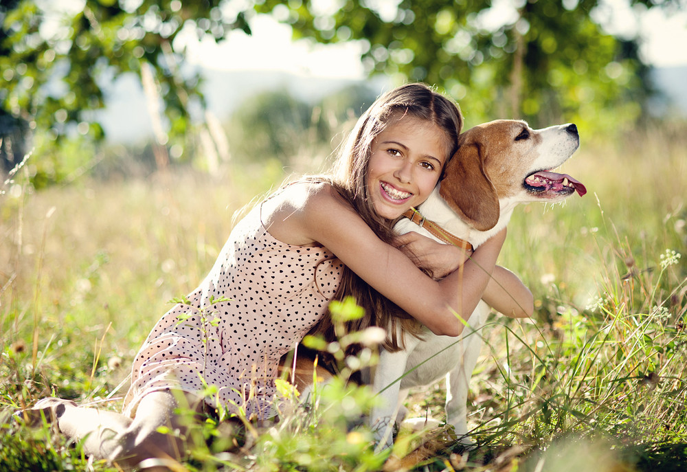Portrait of a teenage girl with her beautiful dog outdoors