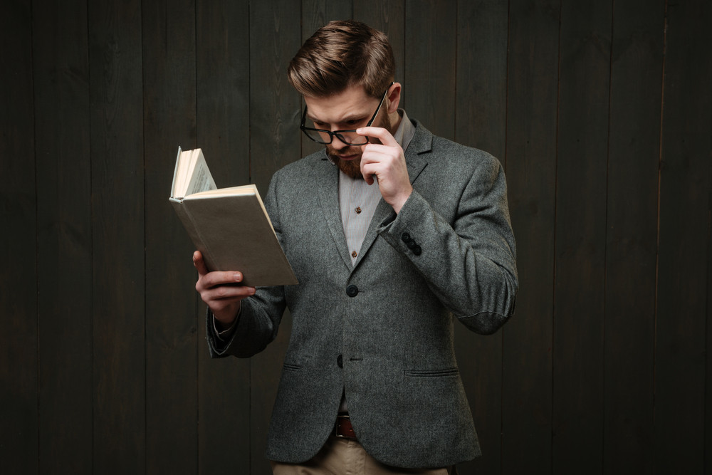 Portrait of a thoughtful bearded man in eyeglasses and jacket reading book isolated on the black wooden background