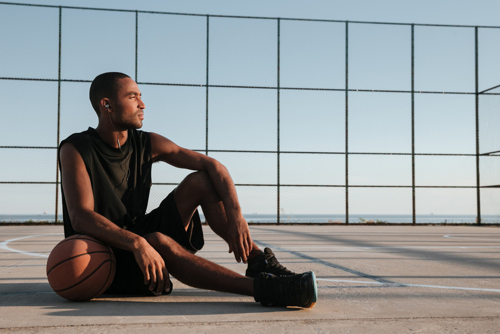 Portrait of a tired african basketball player resting after game at the playground