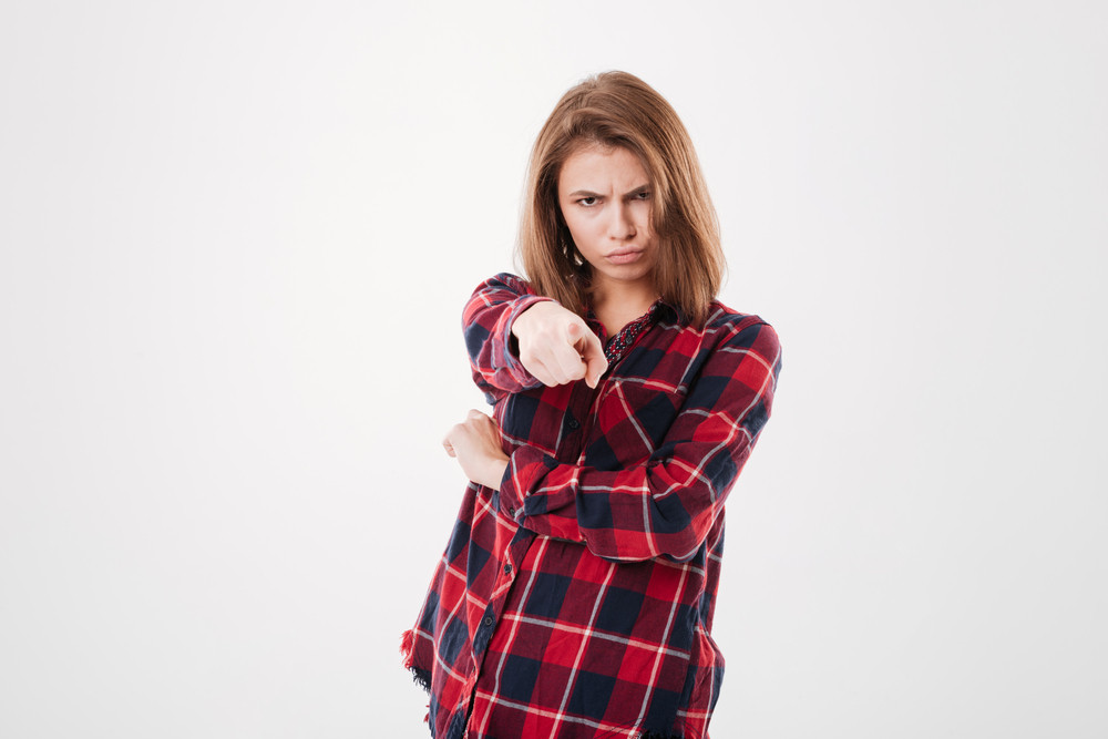 Portrait of a young angry woman in plaid shirt pointing finger at camera isolated on a white background