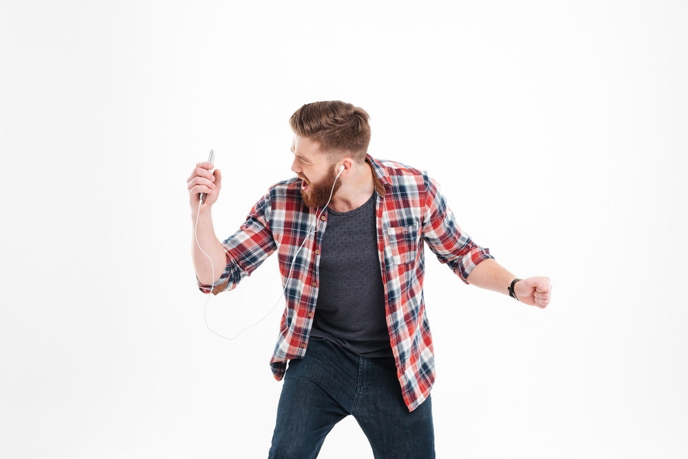 Portrait of a young bearded man listening music with earphones and dancing isolated on a white background